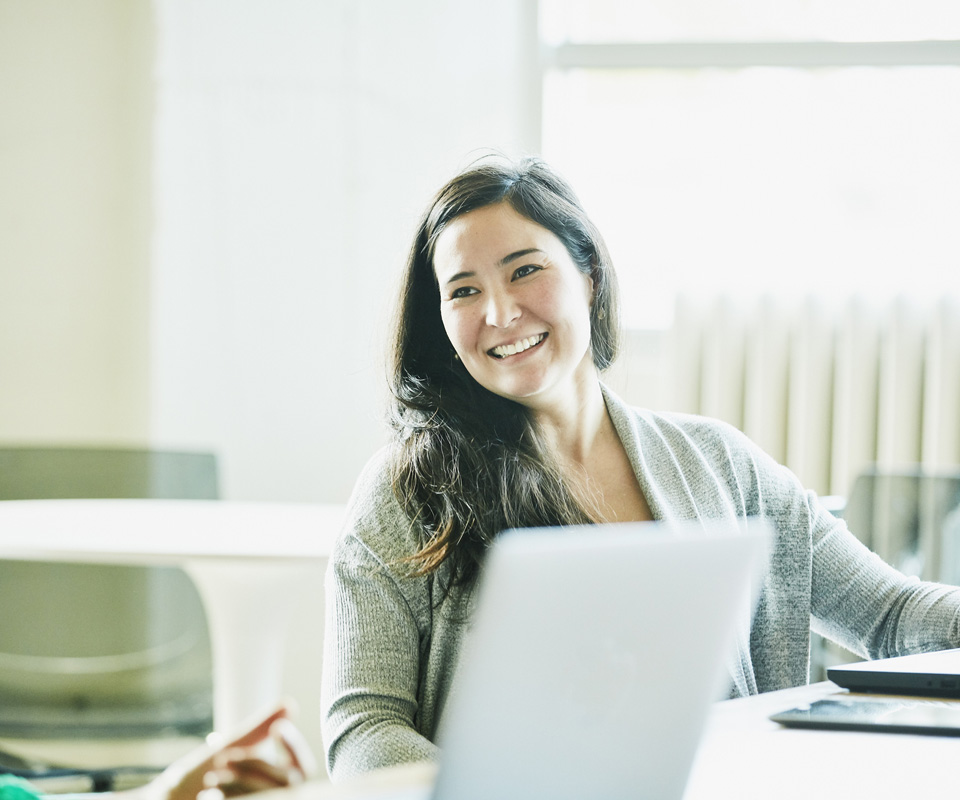 Smiling woman at work with laptop