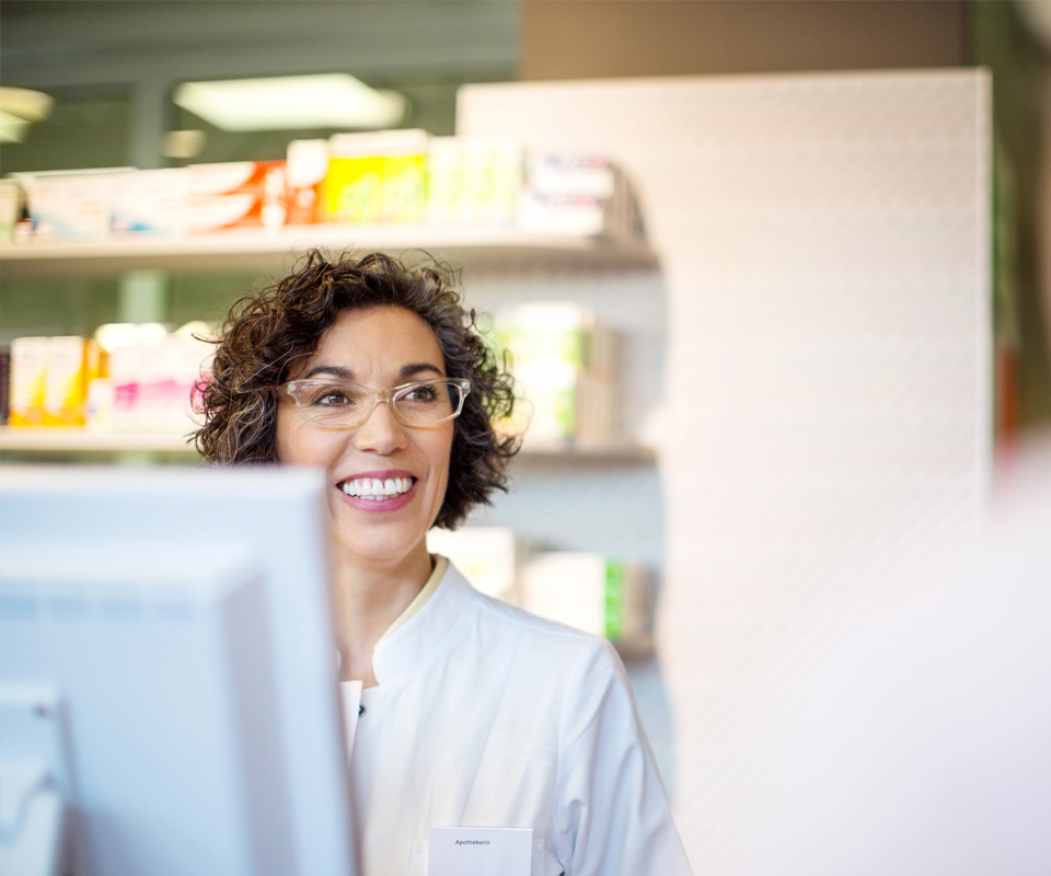 Woman smiling from pharmacy counter